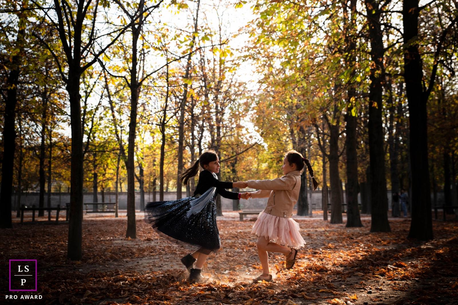 Paris Ile-de-France Lifestyle Family Portrait Photographer | Image contains: girls, hands, swinging, leaves, trees, park, play