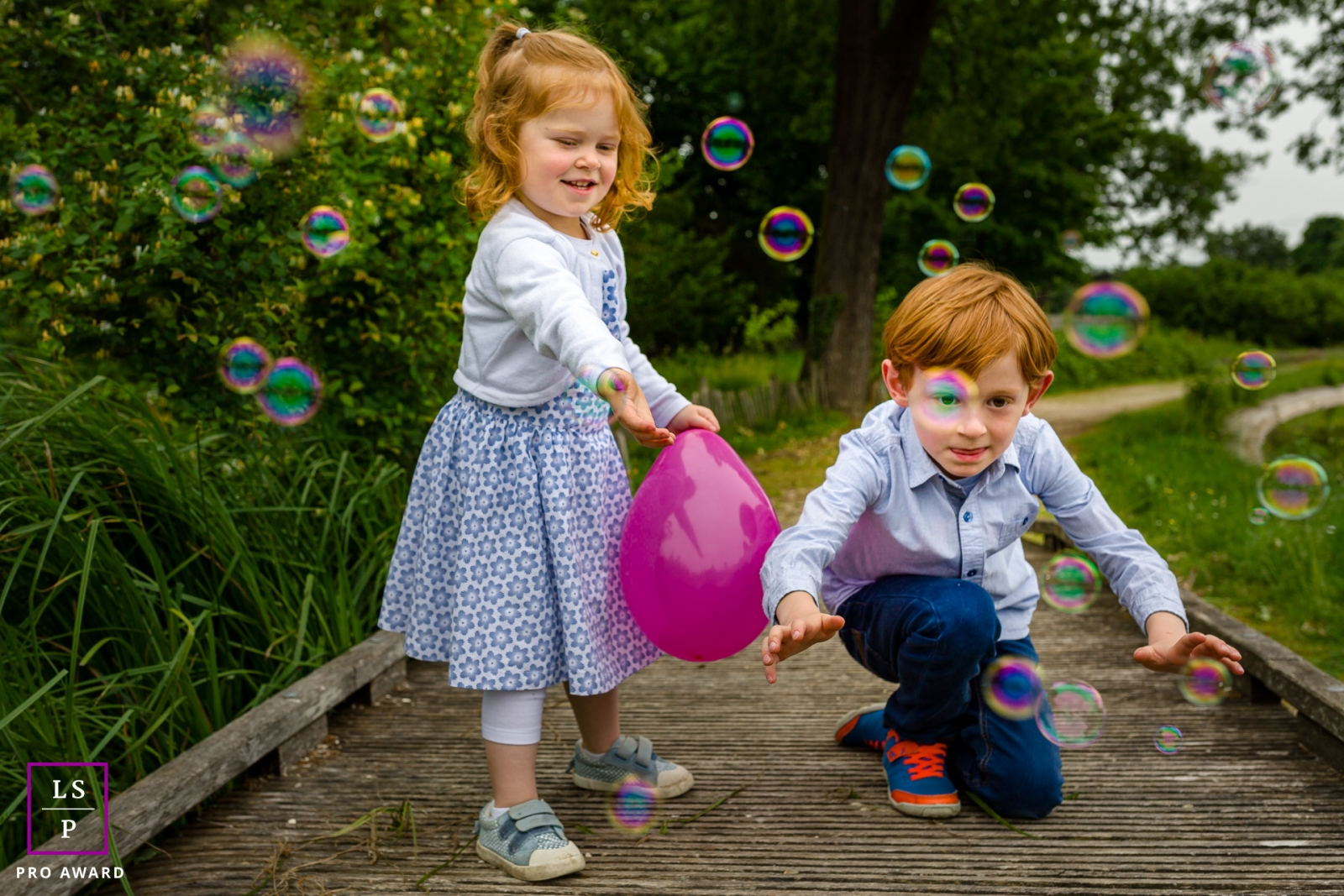 Family Portraits in Ile-de-France   Lifestyle Photography Session: Brother and sister catching soap bubbles