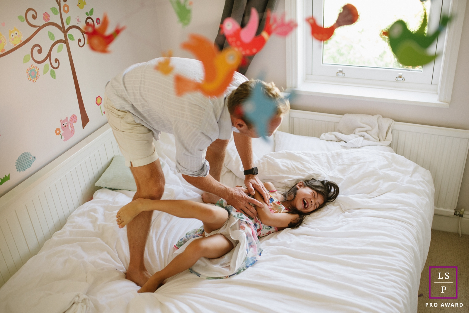 Lifestyle Family Portraits in East Sussex England - Photo contains: dad, girl, bed, tickling, window, birds