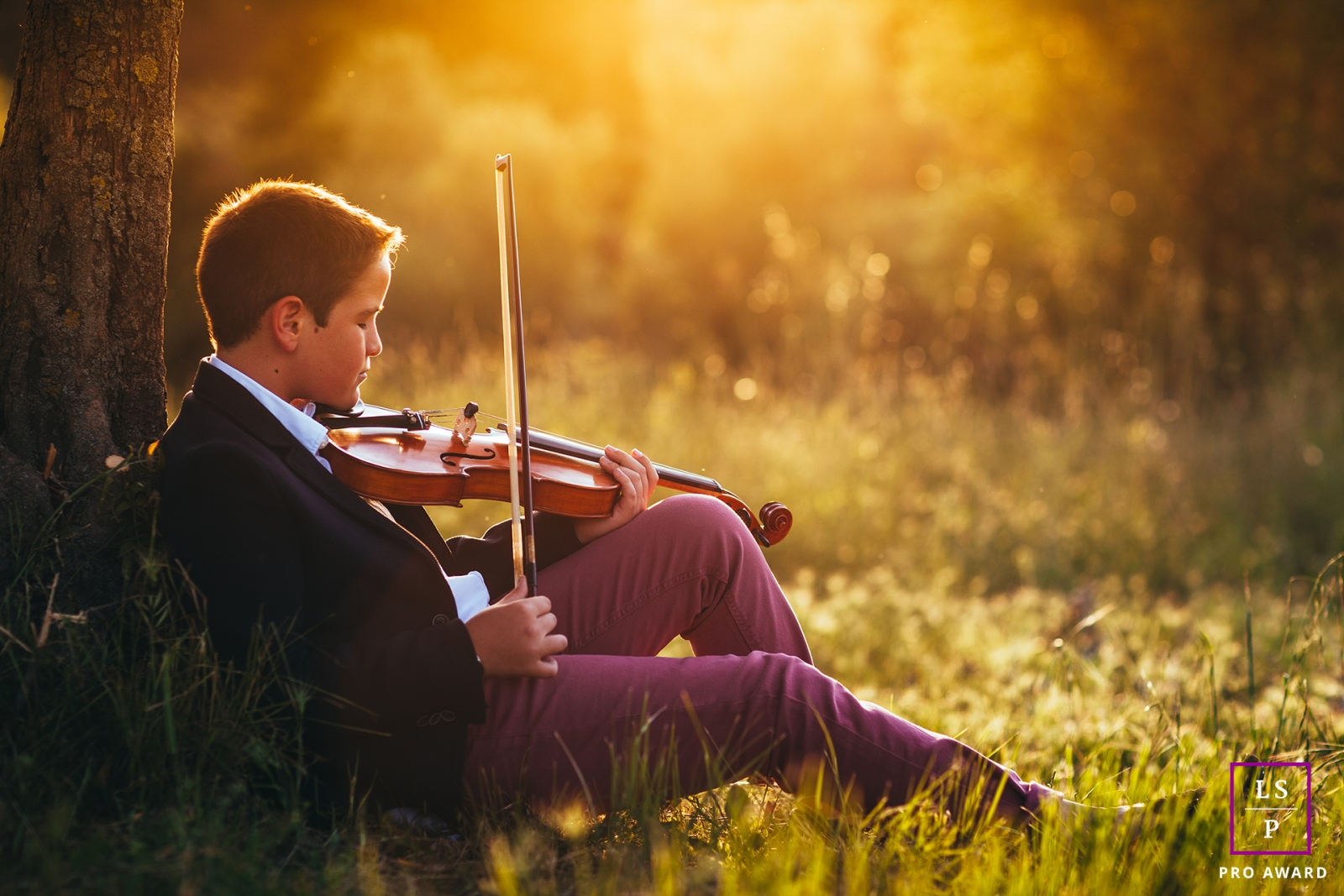Boy Portraits in Barcelona Spain | Lifestyle Photography Session contains: young man, grass, tree, violin, sunlight