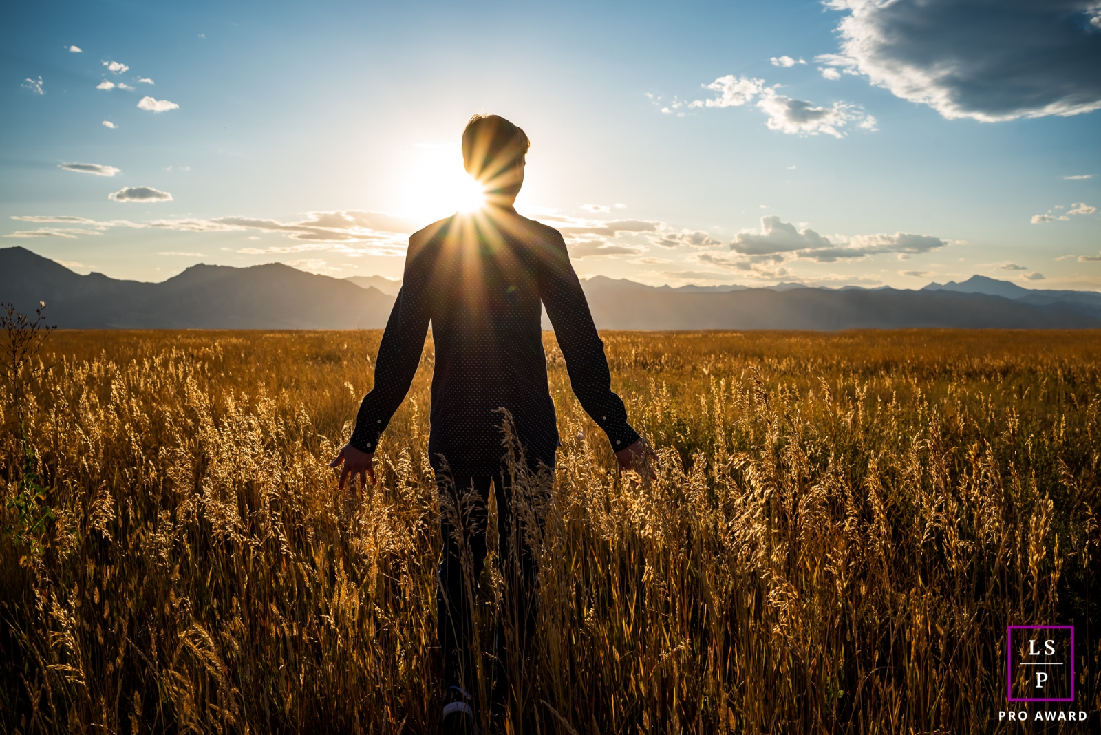 A Boulder High school senior boy poses in the golden light in front of the rocky mountains during a lifestyle portrait shoot in Colorado